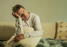 Hombre triste y desesperado joven en casa que se sienta en el sofá del sofá que lleva a cabo la depresión y la tensión sufridoras Fotos de archivo libres de regalías