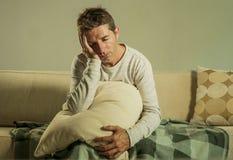 Hombre triste y desesperado joven en casa que se sienta en el sofá del sofá que lleva a cabo la depresión y la tensión sufridoras Foto de archivo libre de regalías