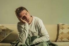 Hombre triste y desesperado joven en casa que se sienta en la depresión y la ansiedad sufridoras del sofá del sofá que sienten pa Foto de archivo libre de regalías