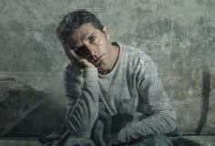 Hombre triste y desesperado joven en casa que se sienta en la depresión y la tensión sufridoras del sofá del sofá que sienten des Imagenes de archivo