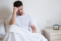 Hombre triste y trastornado que despierta por la mañana Foto de archivo libre de regalías