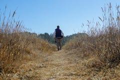 Hombre tropical de la lluvia que camina sobre un campo en una chaqueta azul y pantalones del caqui foto de archivo