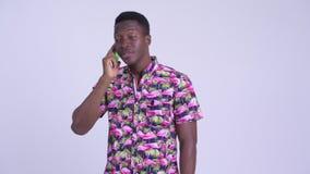 Hombre turístico africano feliz joven que habla en el teléfono almacen de video