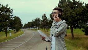 Hombre turístico con el bolso grande y algunos ficheros en manos en el camino que habla en el teléfono y la sonrisa metrajes