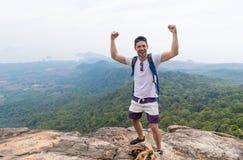 Hombre turístico con la mochila que se coloca en la sonrisa feliz aumentada superior de las manos de la montaña sobre paisaje her fotografía de archivo libre de regalías