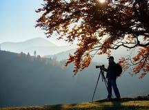 Hombre turístico del caminante con la cámara en el valle herboso en el fondo del paisaje de la montaña debajo del árbol grande fotografía de archivo libre de regalías