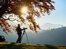 Hombre turístico del caminante con la cámara en el valle herboso en el fondo del paisaje de la montaña debajo del árbol grande foto de archivo