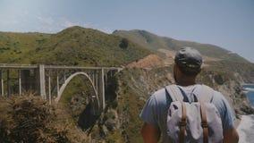 Hombre turístico emocionado feliz joven con la mochila que mira el paisaje hermoso épico del puente del barranco de Bixby, yéndos almacen de metraje de vídeo