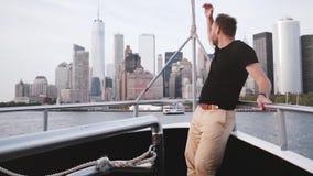 Hombre turístico emocionado feliz que sonríe, disfrutando de la opinión del horizonte de la isla de Manhattan en Nueva York de un almacen de metraje de vídeo