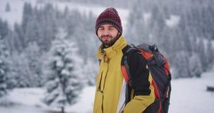 Hombre tur?stico feliz grande sonriente delante de la c?mara ?l que viaja en la monta?a, en el paisaje que sorprende del invierno almacen de video