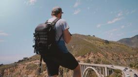 Hombre turístico feliz joven del fotógrafo con la mochila profesional que mira paisaje épico en el puente California del barranco almacen de video