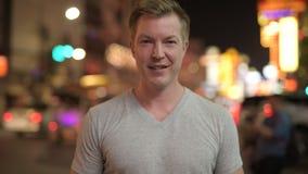Hombre turístico feliz joven que sonríe contra la vista de las calles en Chinatown en la noche almacen de metraje de vídeo