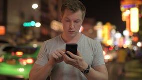 Hombre turístico feliz joven usando el teléfono contra la vista de las calles en Chinatown en la noche almacen de video
