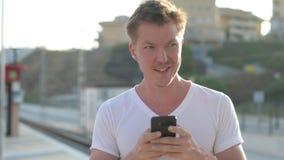 Hombre turístico feliz joven usando el teléfono mientras que espera en la estación de tren almacen de video