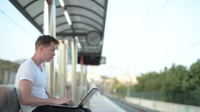Hombre turístico hermoso joven que sienta y que usa el ordenador portátil mientras que espera el tren metrajes