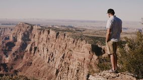 Hombre turístico joven acertado feliz que mira el paisaje épico sobre las montañas de Grand Canyon, tiro cinemático ancho del fon metrajes