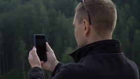 Hombre turístico joven con el teléfono celular elegante que toma el selfie de la imagen de la naturaleza asombrosa almacen de metraje de vídeo