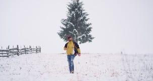 Hombre turístico joven feliz y sonriente que camina a través del campo nevoso, él que disfruta invierno mientras que viaja solame almacen de metraje de vídeo