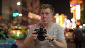 Hombre turístico joven que fotografía con la cámara en las calles de Chinatown en la noche almacen de video