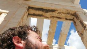 hombre turístico que camina con ruinas antiguas del templo de la acrópolis, Atenas, Grecia metrajes