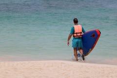Hombre turístico que disfruta del soporte encima del tablero de paleta o de la tabla hawaiana en t fotos de archivo