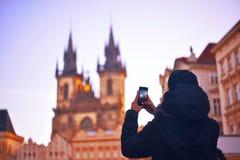Hombre/turista que toma las fotos de un monumento con el teléfono móvil praga Hombre joven con la mochila, tomando imágenes de la Fotos de archivo