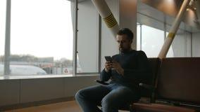 Hombre urbano de la barba que usa el teléfono elegante que viaja dentro en aeropuerto Modelo masculino hermoso almacen de video
