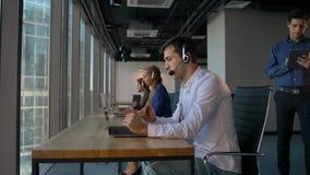 Hombre usando auriculares mientras que trabaja en oficina del centro de atención telefónica metrajes