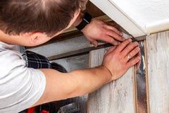 Hombre usando codo y el lápiz de medición mientras que instala el nuevo suelo laminado de madera en casa foto de archivo