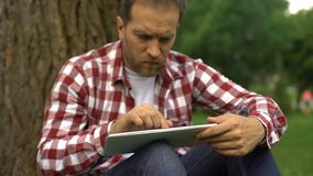Hombre usando el app de la actividad bancaria en línea en la tableta, los términos favorables y el interés, necesidad del dinero almacen de video