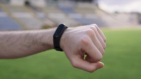 Hombre usando el dispositivo del perseguidor de la pulsera del deporte de la aptitud en su cierre de la mano para arriba almacen de metraje de vídeo