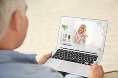 Hombre usando el ordenador port?til para la consulta en l?nea con el doctor v?a la charla video en casa foto de archivo