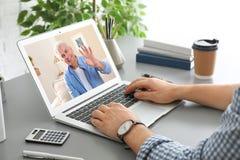 Hombre usando el ordenador portátil para la conversación vía la charla video en la tabla foto de archivo