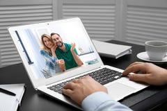 Hombre usando el ordenador portátil para la conversación vía la charla video en la tabla imágenes de archivo libres de regalías