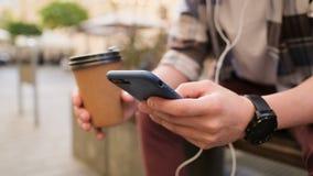Hombre usando el smartphone y el café de consumición a ir al aire libre Primer Generación z en equipo del inconformista, usando s almacen de metraje de vídeo