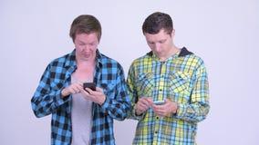 Hombre usando el teléfono y el parecer culpable con la risa del hombre joven almacen de video