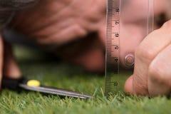 Hombre usando escala de medición mientras que corta la hierba foto de archivo libre de regalías