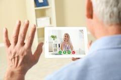 Hombre usando la tableta para la consulta en l?nea con el doctor v?a la charla video en casa foto de archivo