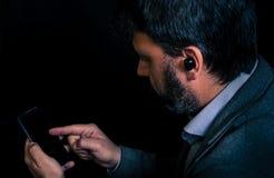 Hombre usando los auriculares del smartphone y del bluetooth fotos de archivo