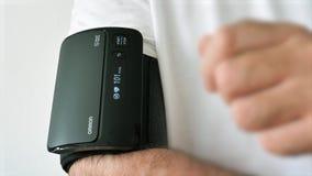 Hombre usando monitor inalámbrico de la presión arterial del brazo superior del bluetooth de Omron Evolv metrajes