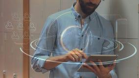 Hombre usando su tableta digital rodeada por la animación tecnológica almacen de video