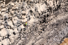 Hombre valeroso joven que sube la pared natural de la roca imagenes de archivo