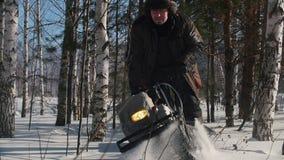 Hombre valeroso que maniobra en mini moto de nieve en las nieves acumulada por la ventisca profundas en el bosque del invierno en almacen de metraje de vídeo