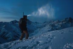 Hombre valiente con el faro, la mochila y una snowboard detrás el suyo noche trasera de la subida en la montaña nevosa El hombre  Fotos de archivo libres de regalías