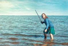 Hombre valiente con la espada en traje escocés Fotografía de archivo libre de regalías