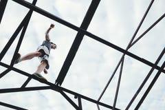 Hombre valiente y aventurado que equilibra en el top de alta construcción metálica fotos de archivo