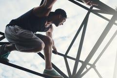 Hombre valiente y aventurado que se sienta en el top de alta construcción metálica imagen de archivo libre de regalías