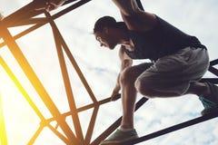 Hombre valiente y aventurado que se sienta en el top del puente del alto metal foto de archivo libre de regalías