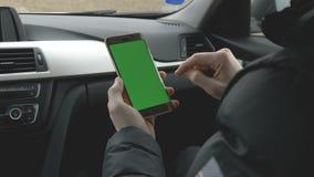 Hombre VERDE de la PANTALLA que sostiene su smartphone en un coche almacen de video