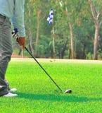 Hombre verde del curso del agujero del golf que pone la bola Imagen de archivo libre de regalías